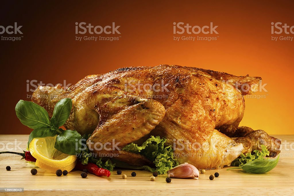 Roasted chicken on a table surrounded by vegetables royalty-free stock photo