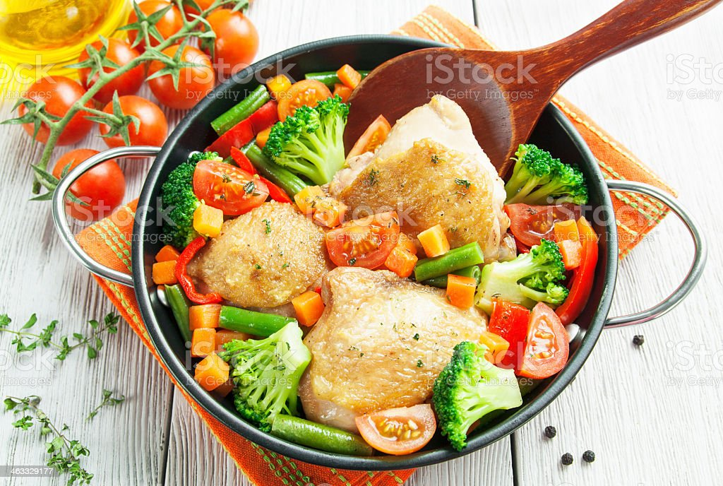Roasted chicken thighs and vegetables being stirred in a pan stock photo