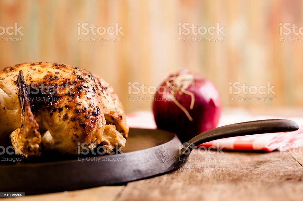 Roasted chicken, turkey with onion in iron skillet. stock photo