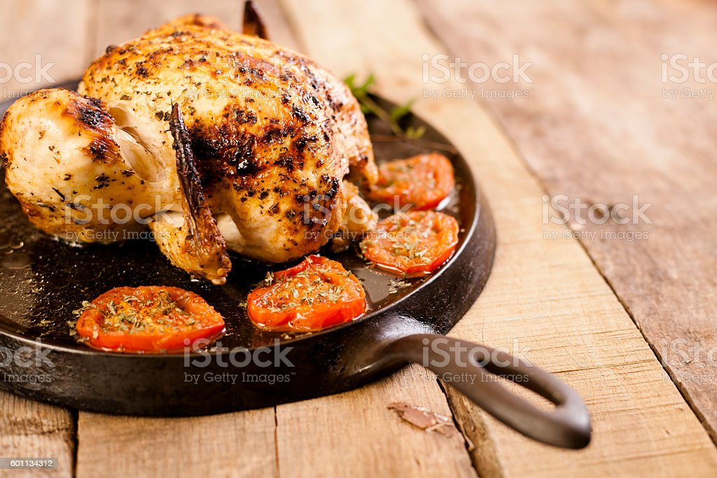 Roasted chicken, turkey with tomatoes in iron skillet. stock photo