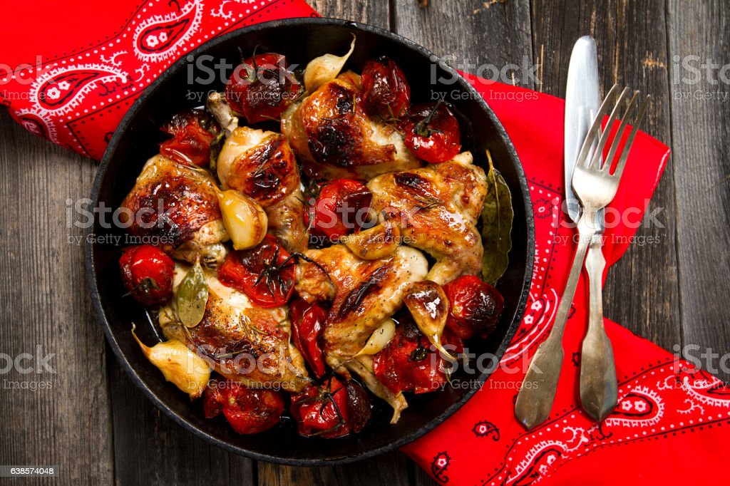 Roasted chicken with garlic, tomatoes and spices stock photo