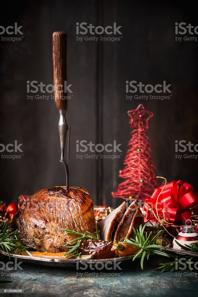 Roasted Christmas ham with fork and red festive holiday decoration stock photo