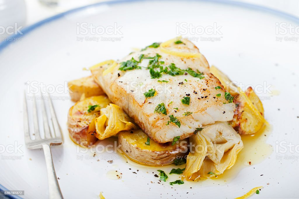 Roasted cod, codfish with baked potatoes and artichokes with sauce stock photo