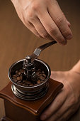 Roasted coffee beans are ground in a coffee grinder