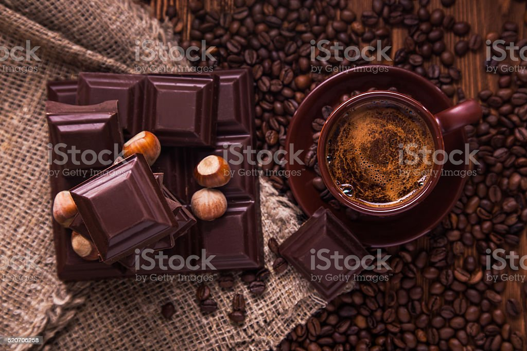 Roasted coffee beans, chocolate, nuts , cup on the wooden background stock photo