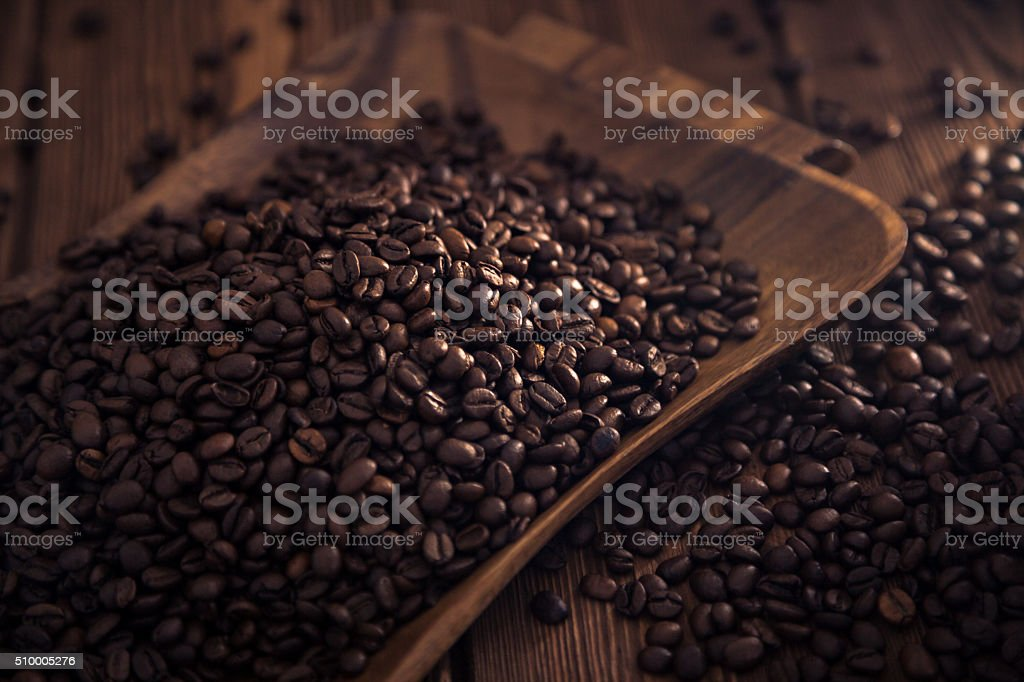 Roasted coffee beans close-up on a wooden surface stock photo