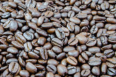 Roasted coffee beans in a sack on a wooden background