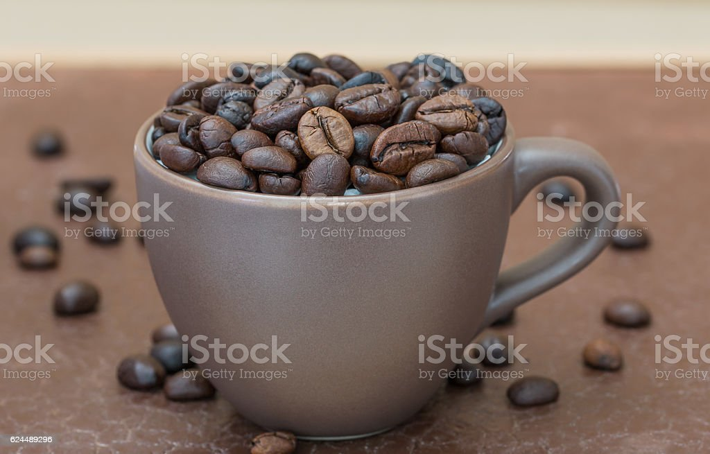 Roasted coffee beans  in brown coffee cup stock photo