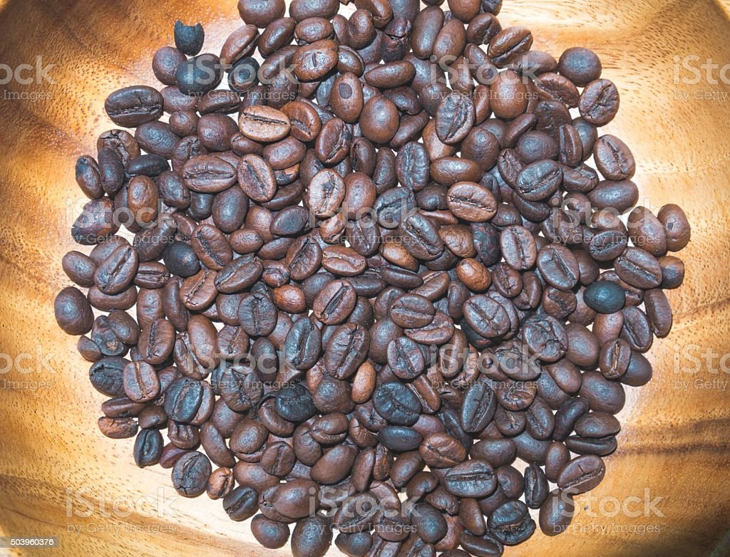 Roasted coffee beans in the wooden plate in vintage style stock photo