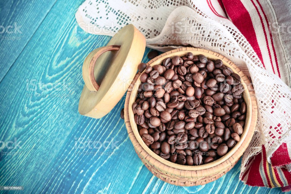 Roasted coffee beans in wooden basket and linen napkin with laceson a wooden background stock photo