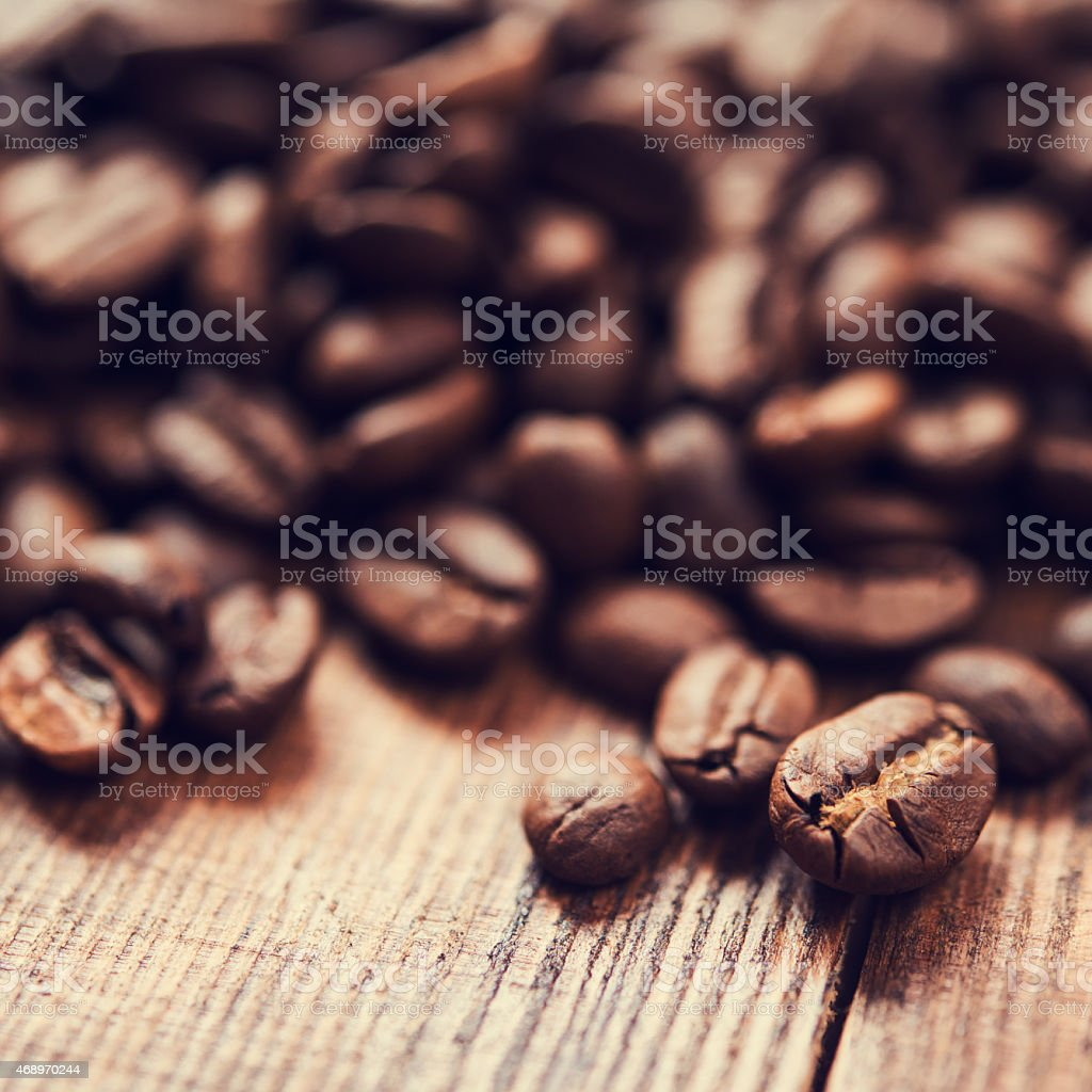 Roasted coffee beans sitting on a plank of wood stock photo