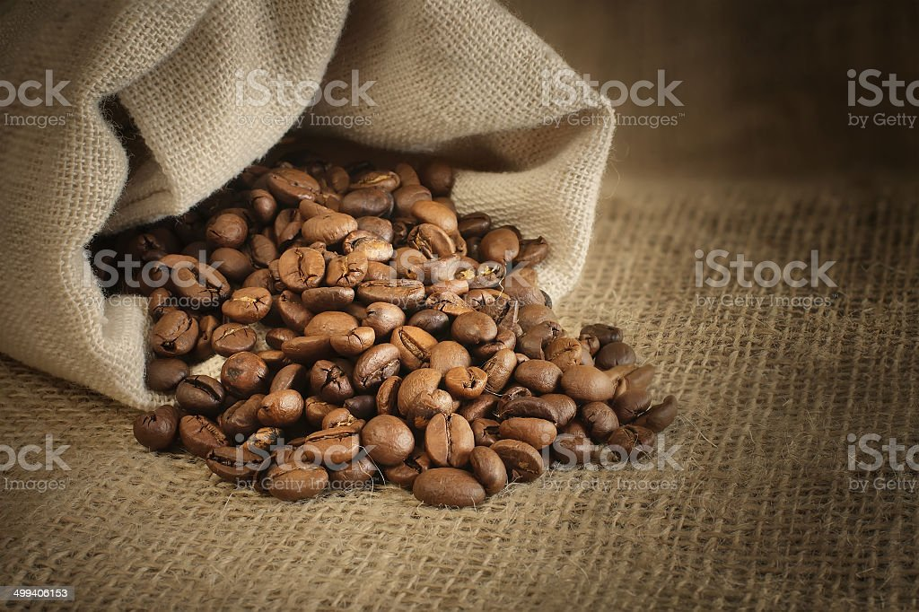 roasted coffee beans spill out of the bag stock photo