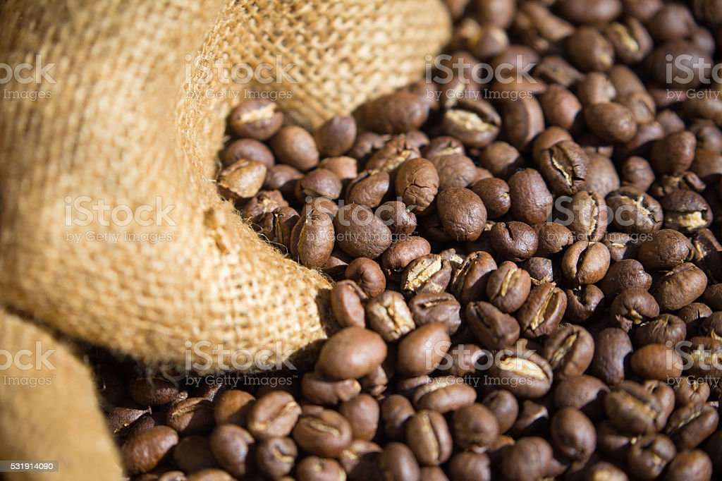 Roasted Coffee beans spilling out of a burlap sack stock photo