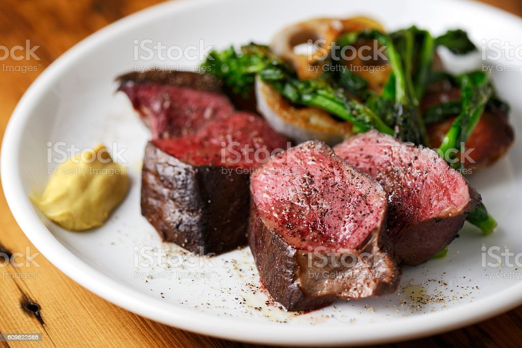 Roasted cubed cow heart on white plate with vegetables stock photo