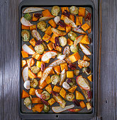 Roasted cut vegetables and fruit on a baking sheet.