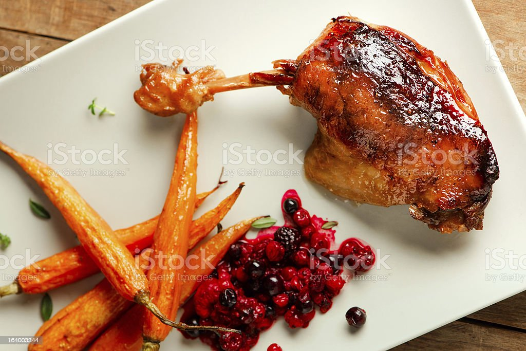 Roasted duck leg with caramelized vegetables and currannt jam. royalty-free stock photo