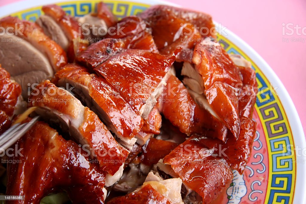 Roasted duck on a Chinese plate on a pink background stock photo