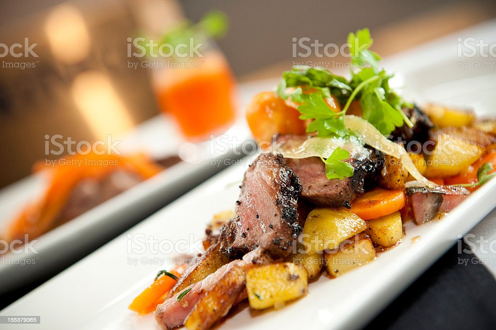 Roasted duck slices served with potatoes and carrots stock photo