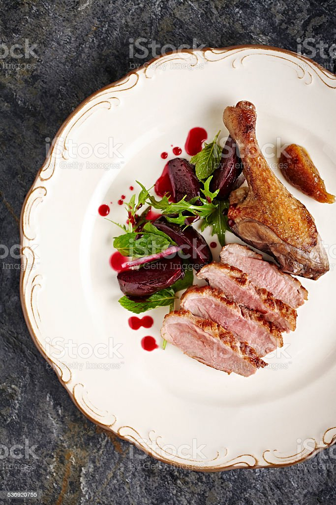 Roasted duckling served with greens and beet stock photo
