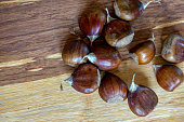 Roasted edible sweet chestnuts on wooden table