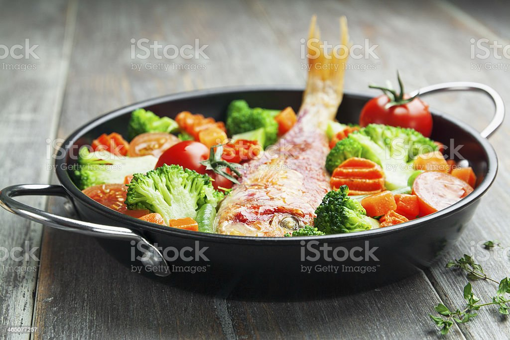 Roasted fish with vegetables stock photo