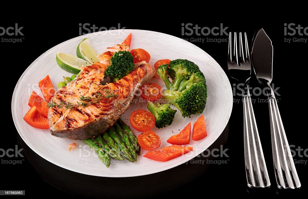 Roasted gilt-head bream with vegetables on plate, isolated over black royalty-free stock photo