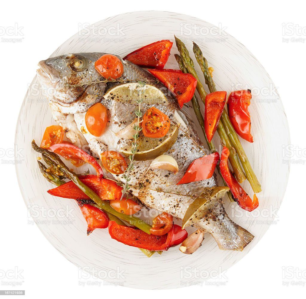 Roasted gilt-head bream with vegetables on plate, isolated over white royalty-free stock photo