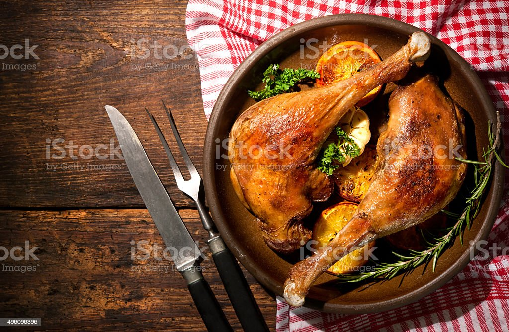 Roasted goose legs with oranges stock photo