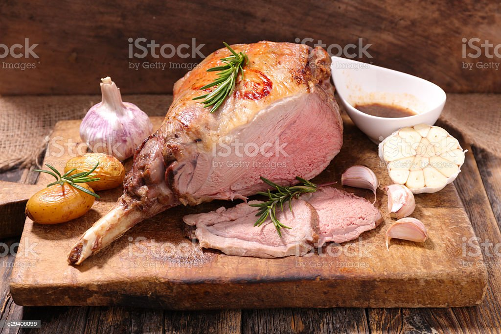 roasted lamb leg on board stock photo