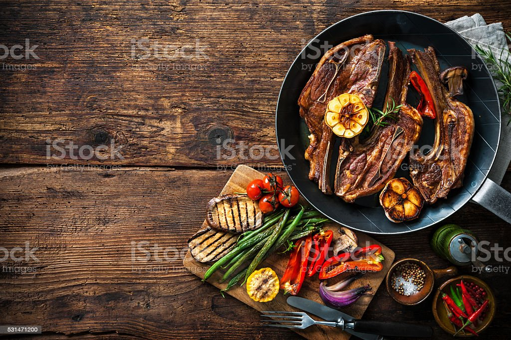 Roasted lamb meat with vegetables on grill pan stock photo