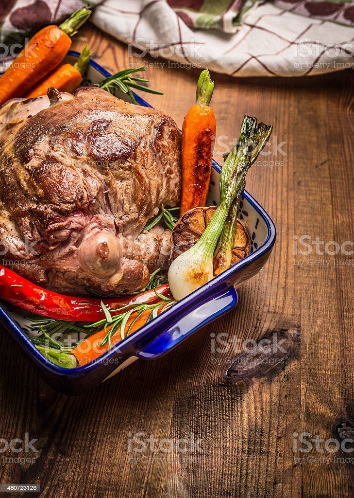 Roasted leg of lamb with herbs and vegetables stock photo