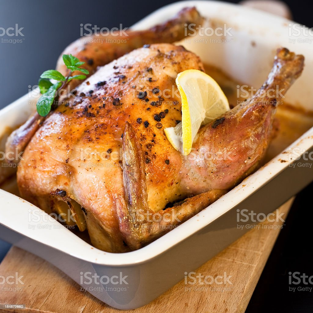 Roasted lemon and mint chicken sitting in pan royalty-free stock photo
