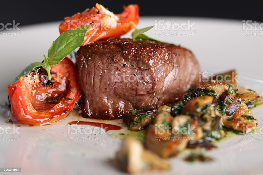 Roasted meat with tomatoes and mushrooms on a white plate stock photo