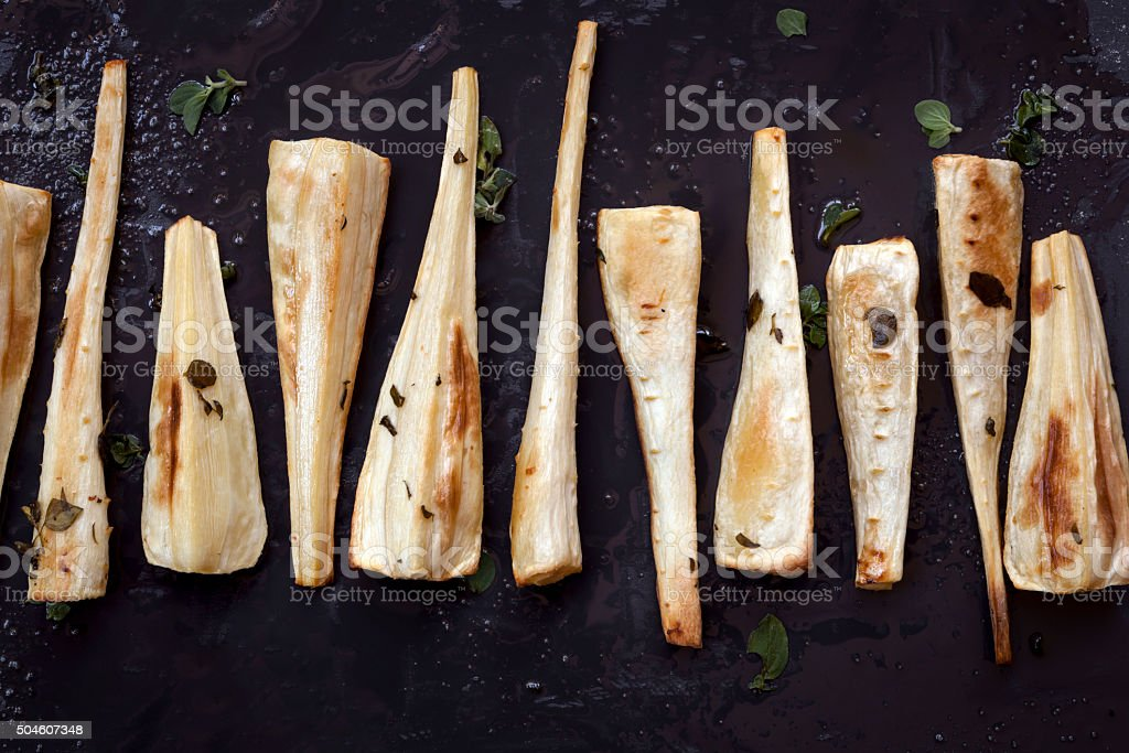 Roasted Parsnips on Black Overhead View stock photo