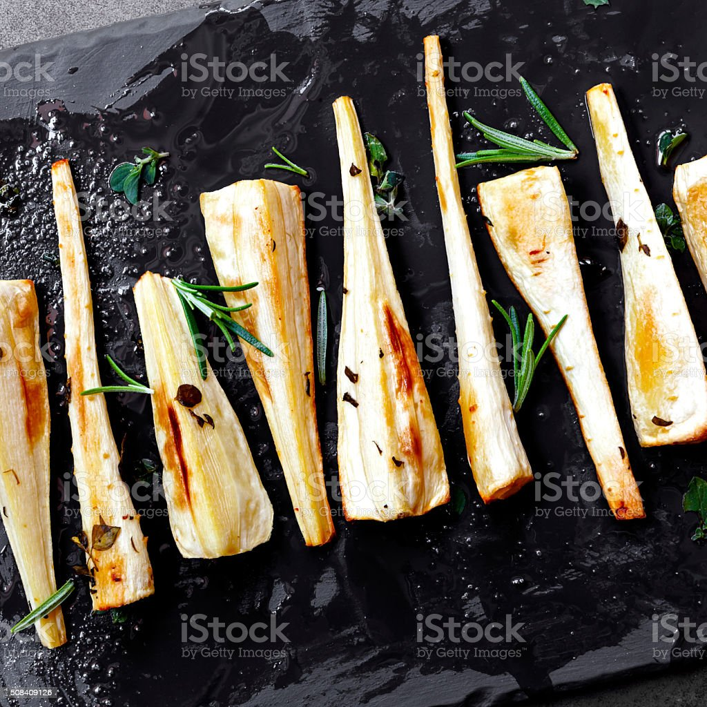 Roasted Parsnips on Slate Overhead View stock photo