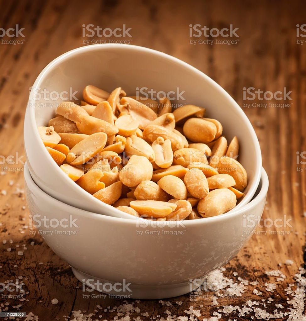 Roasted peanuts and salt in a bowl on wooden background stock photo