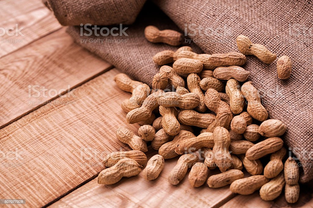 Roasted peanuts in shell on wooden table stock photo
