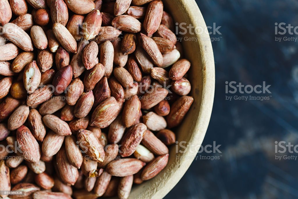 Roasted peanuts in wooden bowl stock photo