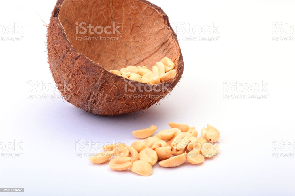 Roasted peeled peanuts in Handmade bowl of coconut, Selective Focus stock photo