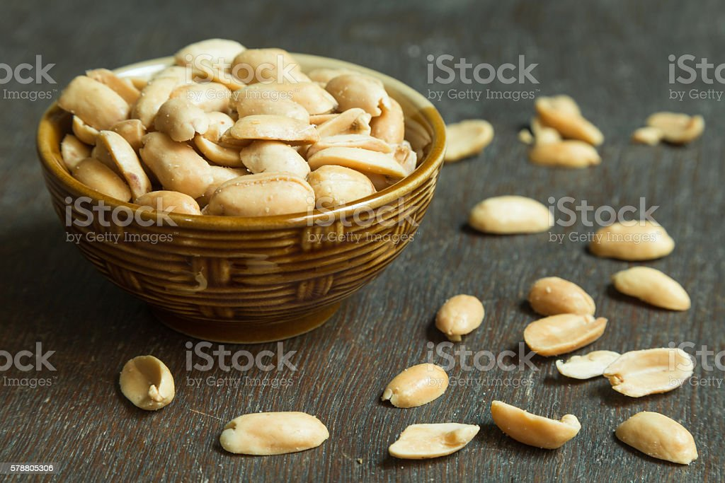 Roasted peeled salted peanuts in rustic bowl on wooden background stock photo