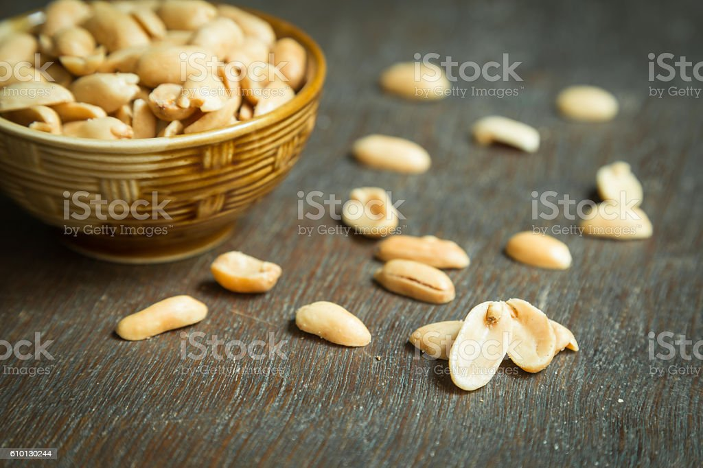 Roasted peeled salted peanuts in rustic bowl , shallow focus stock photo