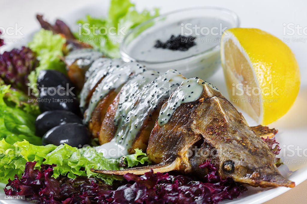 Roasted pike under white sauce with black caviar stock photo