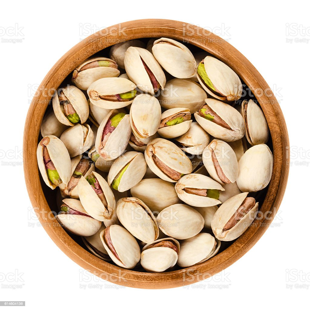 Roasted pistachio seeds with shell in bowl over white stock photo