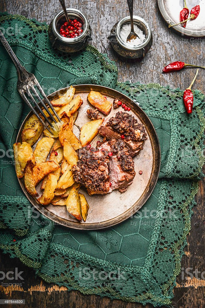 Roasted Pork fillet with crust and baked potato in plate stock photo