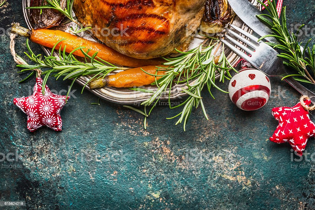 Roasted pork ham  with vegetables , cutlery  and Christmas decoration stock photo