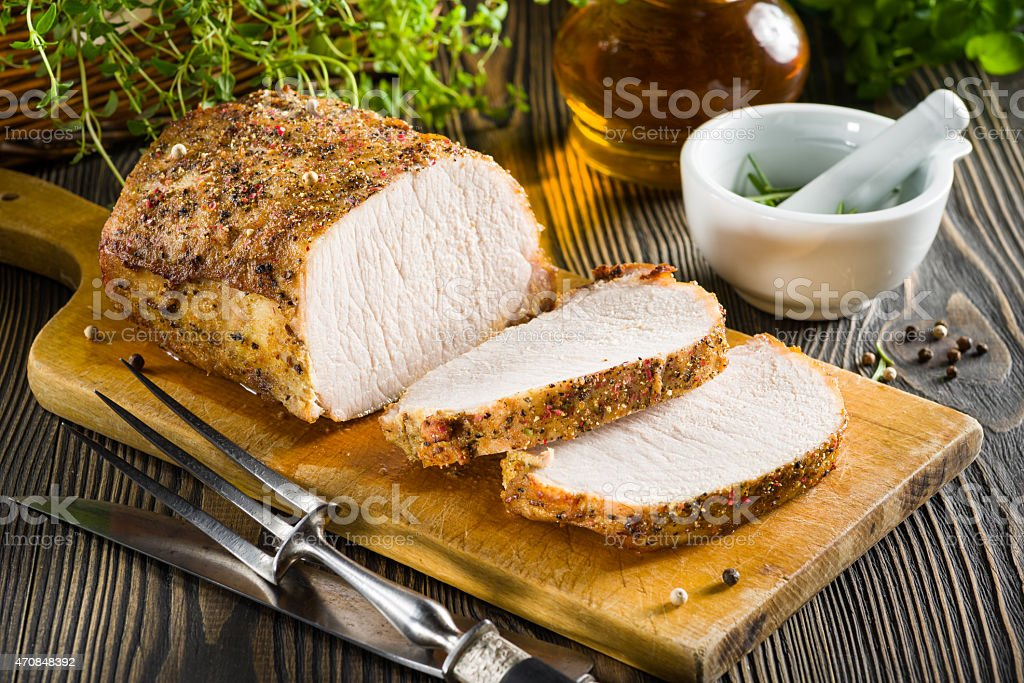 Roasted pork loin on the wooden table stock photo