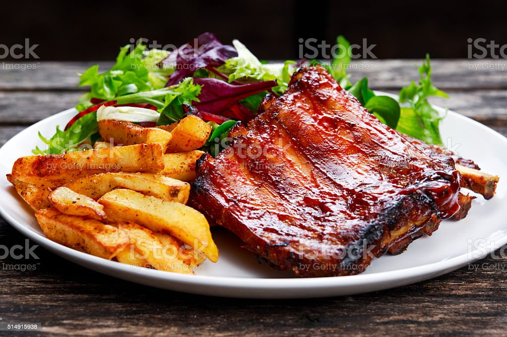 Roasted Pork Rib, Fried Potato on white plate with Vegetables. stock photo
