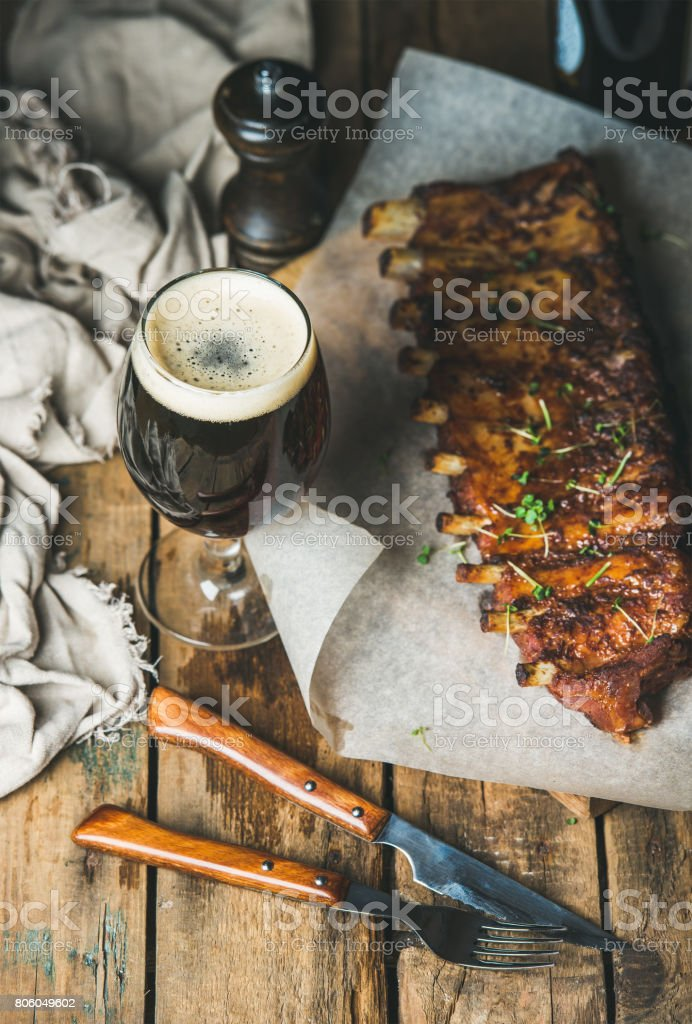 Roasted pork ribs with garlic, rosemary and glass of beer stock photo