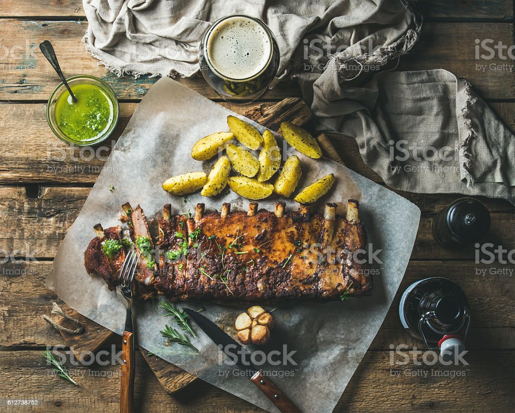Roasted pork ribs with sauce, fried potato and dark beer stock photo