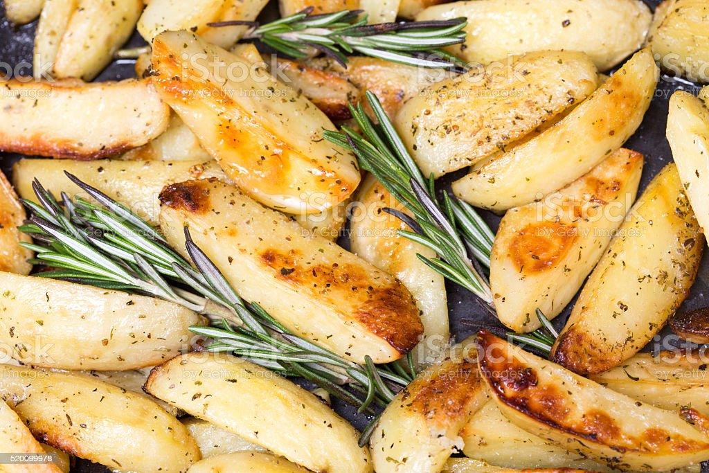 Roasted potato wedges with rosemary on a baking tray stock photo